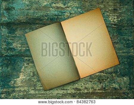Open Old Book On Grungy Wooden Background. Paper Texture
