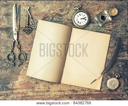 Open Journal Book And Vintage Writing Tools On Wooden Table