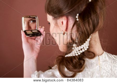 Young Woman Looking Into A Small Mirror