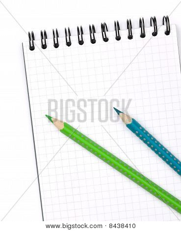 Two Color Pencils On Notepad