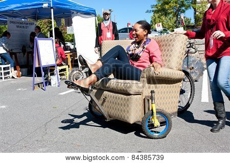 Woman Steers Oddball Furniture Piece On Wheels At Unique Fair