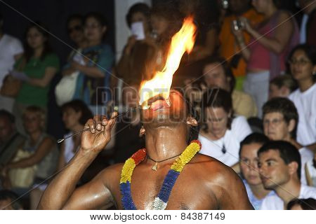Fire Dancer Keeps His Tongue To The Torch At The  Festival Pera Hera In Candy