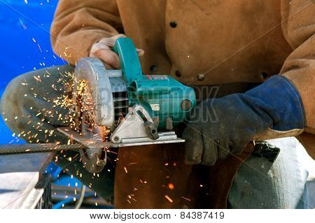 Sparks Fly As Man Cuts Rebar With Power Saw