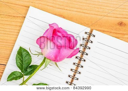 Pink Rose And Diary On Wooden Background