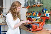 picture of sawing  - Caucasian teenage girl operating scroll saw in technical classroom - JPG