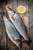 stock photo of sea salt  - two raw fresh sea bass on a cutting board with lemon and sea salt on wooden rustic table - JPG