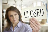 foto of local shop  - Store Owner Turning Closed Sign In Shop Doorway - JPG