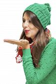 image of sweethearts  - Romantic pretty young woman in a knitted green winter outfit blowing a kiss across the palm of her hand to her sweetheart or while flirting isolated on white - JPG