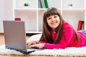 foto of pre-adolescent girl  - Cute little girl is using laptop at her home - JPG