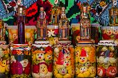 pic of traditional  - Jars with pickles and bottles with alcohol traditional from area Maramures Romania displayed on a background with traditional embroidery - JPG