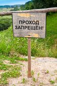 stock photo of ravines  - Old wooden sign with Russian text label means passage is not allowed stands on the edge of the ravine - JPG