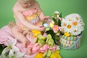 stock photo of baby easter  - Baby in Easter outfit holding Easter eggs tulip flowers on pink blanket - JPG
