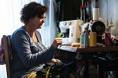 foto of sewing  - Middle aged woman sewing in a sewing workshop - JPG