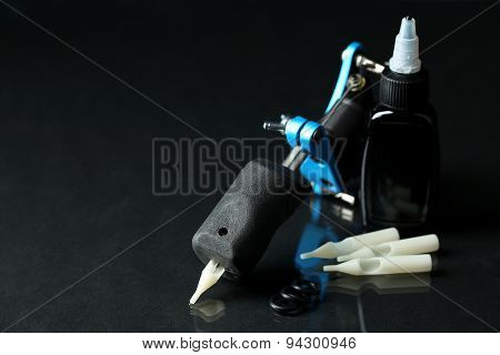 Tattoo machine and tattoo Supplies, on dark background