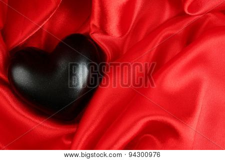 Black heart on fabric background