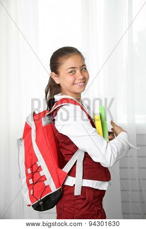 Beautiful little girl in school uniform with backpack and books