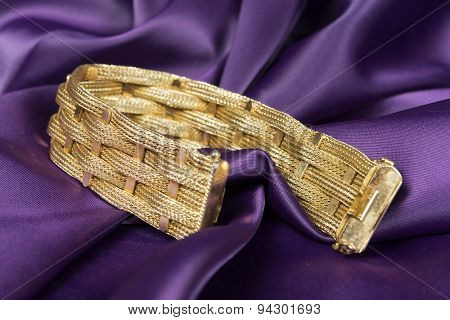 Gold bracelet isolated on purple satin background.