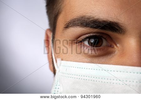 Young male doctor on gray background
