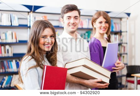 Portrait of three smiling students in a library