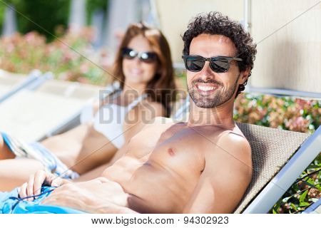 Young couple relaxing on deck-chairs