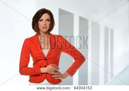 Portrait of beautiful businesswoman in red jacket inside office building