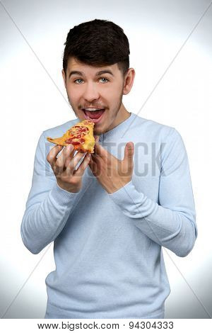 Young man eating piece of pizza on gray background