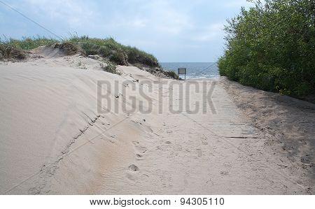 Pedestrian beach boardwalk with sand and sky