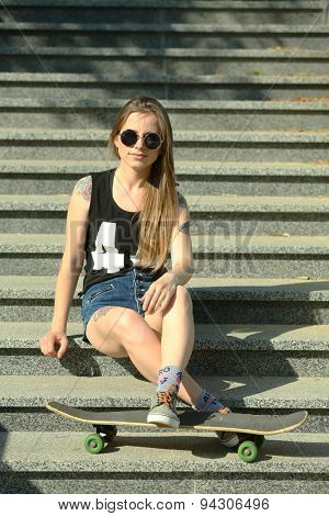 Beautiful tattooed girl with skateboard  on stairs, outdoors
