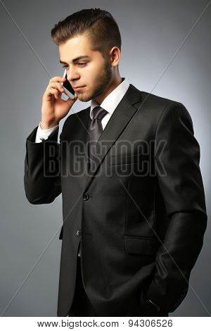 Handsome businessman talking on phone on gray background