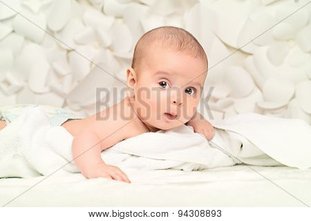 Angelic little baby lying on white blanket. Healthcare. Happy childhood. Background of tender white flowers.
