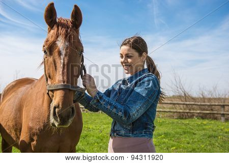 Happy Beautiful Brunette Taking Care Of Her Brown Horse