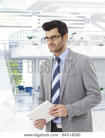 Young businessman in business hall, walking holding tablet.