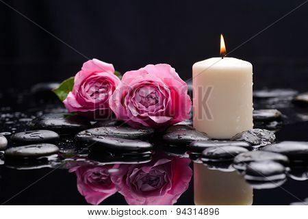 Pink rose with candle and therapy stones