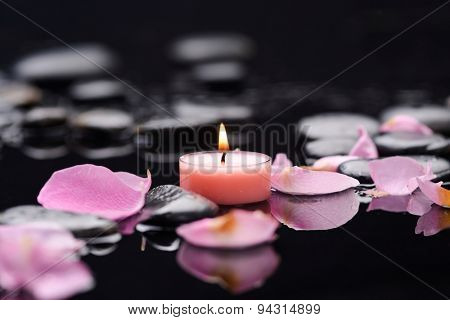 Beautiful rose petals with candle and therapy stones