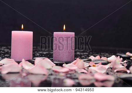 Beautiful rose petals with two candle and therapy stones