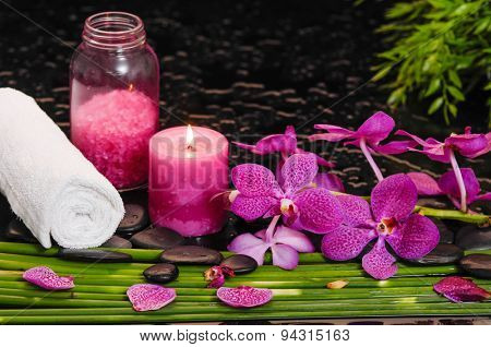 Still life with pink orchid and candle, oil, towel with row of plant stem