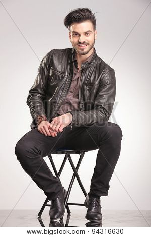 Smiling young fashion man sitting on a chair while looking at the camera.