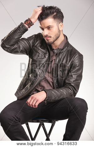 Side view of a young handsome fashion man fixing his hair while sitting on a chair.