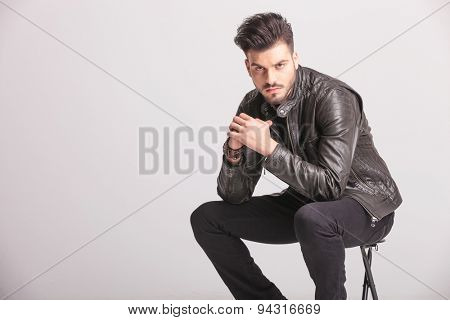 Side view picture of a handsome casual man holding his hands together while sitting on a stool.