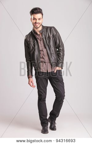 Happy young fashion man walking with his hand in pocket on studio background.