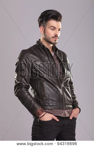 Side view of a young handsome casual man looking away with his hands in pockets.