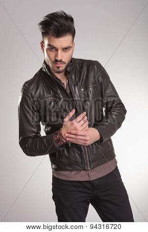 Portrait of a handsome young casual man looking at the camera while holding his hands together.