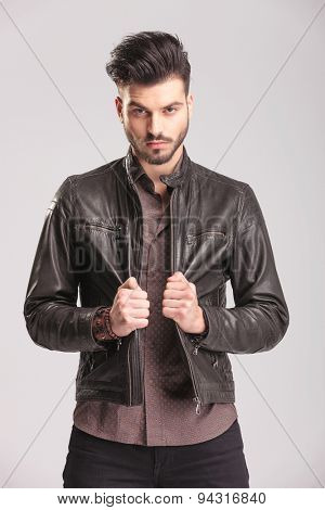 Portrait of a young handsome man pulling his leather jacket while looking at the camera.