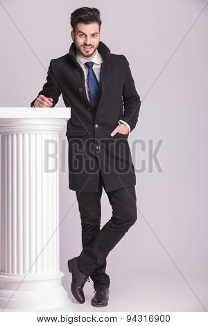 Full lenght picture o a happy young business man leaning his hand on a white column.