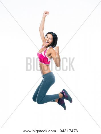 Smiling sporty woman jumping isolated on a white background. Looking at camera