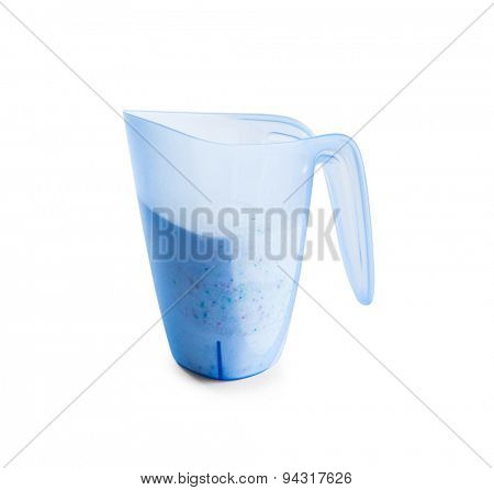 washing powder in a measuring cup on a white background