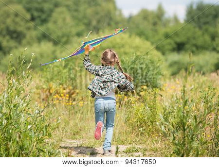 little cute girl flying a rainbow kite in a meadow on a sunny day. back view