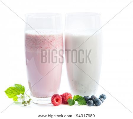 two glasses of milkshake, berries and green twig of raspberry and blueberry isolated on white background
