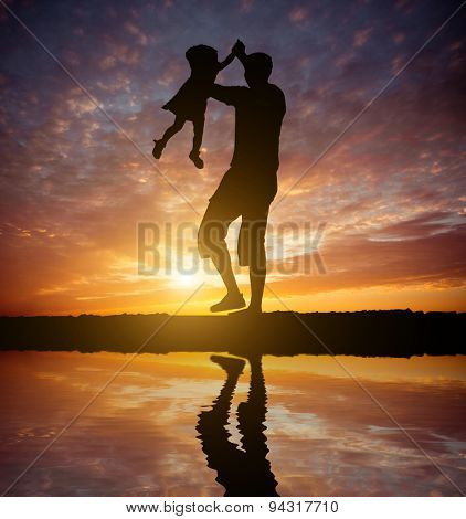 Dad playing with baby daughter on the beach at sunset. Silhouette photo