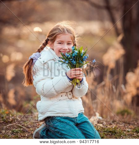 happy little girl in the forest holding a bouquet of snowdrops